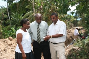Minister responsible for Public Utilities and Natural Resources on Nevis Hon. Carlisle Powell during a site visit at Stoney/Hill (centre) and Health Advisor Mrs. Patricia Hanley (r) get an update of the water project at Stoney Hill from Acting Manager of the Nevis Water Department Mr. George Morris (l). Also present but out of picture are Permanent Secretary Mr. Ernie Stapleton and his assistant Mr. Wakely Daniel